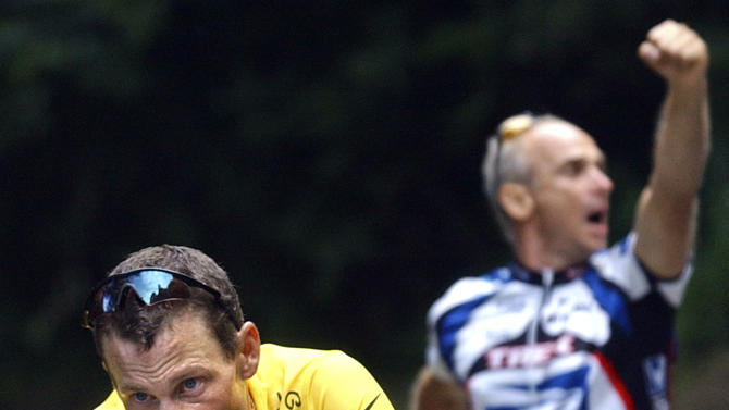 FILE - In this July 21, 2003, file photo, a spectator cheers on Lance Armstrong, left, of the United States, in the final ascent towards Luz-Ardiden during the 15th stage of the Tour de France cycling race between Bagneres-de-Bigorre and Luz-Ardiden, French Pyrenees. In 2003, Armstrong was named the Associated Press Male Athlete of the Year, ESPN's ESPY Award for Best Male Athlete and BBC Sports Personality of the Year Overseas Personality. (AP Photo/Christophe Ena, File)