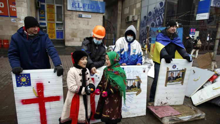 Traditionally dressed children sing to pro-EU demonstrators standing guard near a barricade during a rally at Independence Square in central Kiev