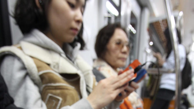 In this Wednesday, Nov. 7, 2012 photo, a passenger plays a game with a smartphone on a subway in Seoul, South Korea. Across the entire population, South Korea's government estimated 2.55 million people are addicted to smartphones, using the devices for 8 hours a day or more, in its first survey of smartphone addiction released earlier this year. (AP Photo/Ahn Young-joon)
