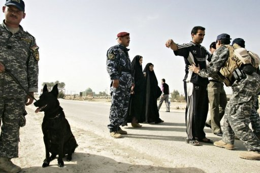 Iraqi police commandos frisk Iraqis in Baquba, in 2010. A suicide bomber killed 22 people at a Shiite gathering in central Iraq, officials said, in the latest in a string of attacks against the Shiite majority that has left dozens dead.