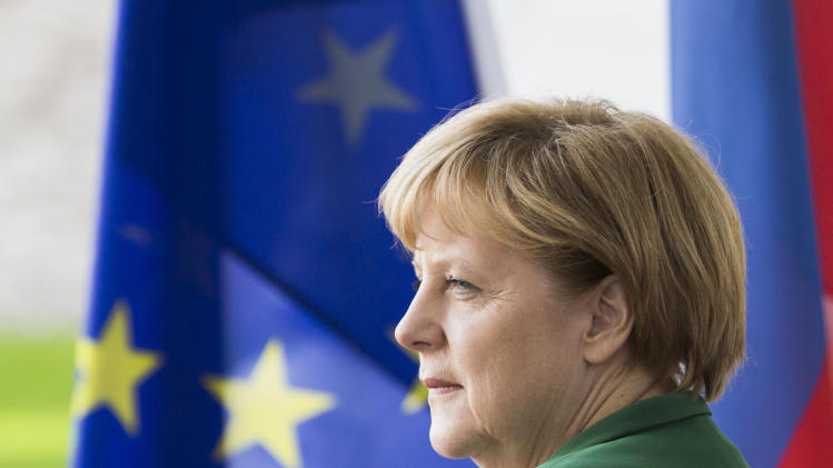 German Chancellor Angela Merkel stands in front of a European flag as she waits for her guest, the President of Slovenia Borut Pahor, unseen, at the chancellery in Berlin, Germany, Thursday, April 25, 2013. (AP Photo/Gero Breloer)