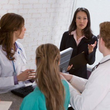 Businesswoman-talking-to-medical-professionals_web