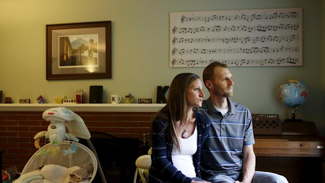 Emily and Matt Knudsen sit in their living room in their home in Fremont