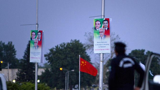 A police officer stands guard next to  billboards welcoming Chinese premier Li Keqiang hung on poles near the presidency in Islamabad, Pakistan. Keqiang will arrive in Islamabad on May 22 on a two day official visit to hold talks with Pakistani leadership to discuss international, regional issues and enhance co-operation in bilateral ties. (AP Photo/Anjum Naveed)