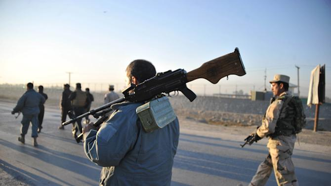 Afghan security forces patrol the site where Taliban suicide bombers attacked a joint U.S.-Afghan air base in Jalalabad, east of Kabul, Afghanistan, Sunday, Dec. 2, 2012. Taliban suicide bombers attacked early Sunday, detonating explosives at the gate and sparking a gunbattle that lasted at least two hours with American helicopters firing down at militants before the attackers were defeated. (AP Photo/Nasrullah Khan)
