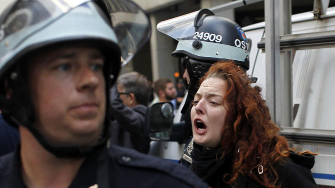 A woman yells out while being arrested during an Occupy Wall Street march, Monday, Sept. 17, 2012, in New York. A handful of Occupy Wall Street protestors were arrested during a march on the New York Stock Exchange on the anniversary of the grass-roots movement. (AP Photo/Jason DeCrow)