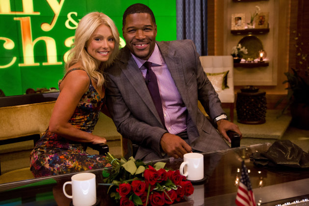 "Former football player Michael Strahan, right, poses Kelly Ripa on the set of the newly named ""Live! with Kelly and Michael"" on Tuesday, Sept. 4, 2012 in New York. Strahan joined the popular morning show as a permanent co-host on Tuesday, fulfilling a joking prophecy he made to Regis Philbin more than four years ago. The gap-toothed former New York Giant jogged onto the morning show set and picked up co-host Kelly Ripa in a bear hug, lifting her off her feet. He replaces Philbin, who left last November. Strahan was the survivor in a series of on-air tryouts of potential co-hosts since Philbin left, and his hiring has been an open secret for the past two weeks. (Photo by Charles Sykes/Invision/AP Images)"