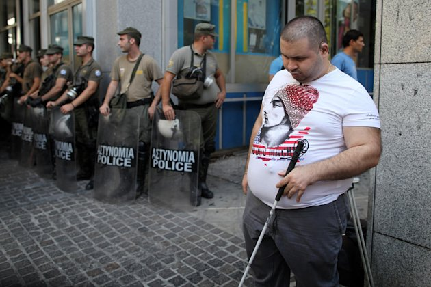 A disabled protester stands in front of riot policemen during a rally outside the Finance Ministry in Athens, on Thursday, Sept. 13, 2012. Disabled groups are angry at likely benefit cuts under a major new austerity program demanded by international rescue creditors. (AP Photo/Petros Giannakouris)