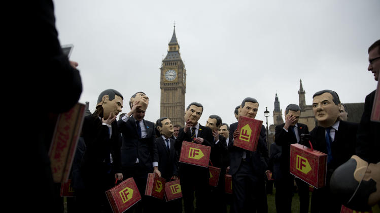 "Campaigners, wearing masks, suits and holding copies of the traditional red ministerial box to represent Britain's Chancellor of the Exchequer George Osborne on budget day, prepare to pose for the media backdropped by the Houses of Parliament as part of a campaign event in Parliament Square, London, Tuesday, March 19, 2013.  The event held Tuesday was organized by the ""IF"" campaign to coincide with the British Finance Minister delivering his annual budget speech to parliament on Wednesday.  The ""IF""campaign, which is a coalition of 170 charities, want the UK and G8 governments to increase agricultural aid spending to help fight poverty and hunger in developing countries.  (AP Photo/Matt Dunham)"