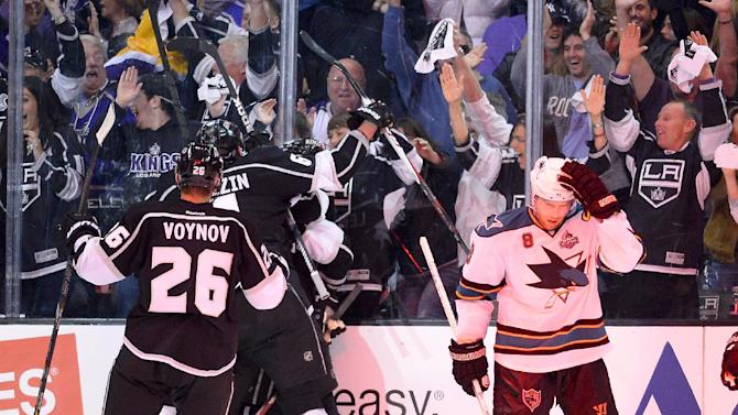 Members of the Los Angeles Kings celebrate center Trevor Lewis's game winning goal as San Jose Sharks center Joe Pavelski skates off during the third period in Game 2 of their second-round NHL hockey Stanley Cup playoff series, Thursday, May 16, 2013, in Los Angeles.  (AP Photo/Mark J. Terrill)