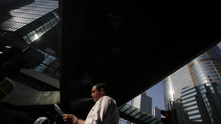 A man smokes in Central, business district, with a backdrop of Hong Kong Stock Exchange, right, Tuesday, Dec. 13, 2011. World stock markets vacillated Tuesday as criticism by ratings agencies sparked doubts about a historic European Union plan to fix a massive debt crisis by binding member economies closer together. (AP Photo/Kin Cheung)