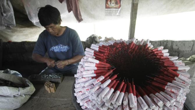 A worker makes fireworks next to unfinished pyrotechnics at a makeshift factory in Bocaue town, Bulacan province
