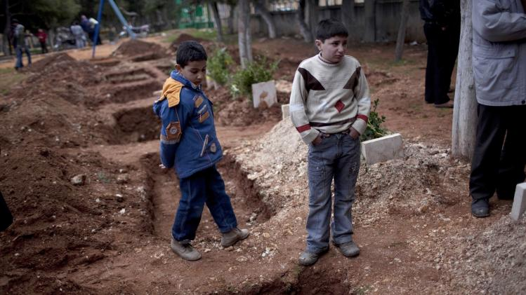 Children attend the funeral of a three Free Syrian Army fighters in a park converted to a cemetery in Idlib, north of Syria, Saturday, March 3, 2012. (AP Photo/Rodrigo Abd)