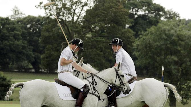 Britain's Duke of Cambridge, Prince William, left, and Prince Harry during the Audi Polo Challenge charity polo match, at Coworth Park, near Ascot, England, Saturday Aug. 3, 2013. Prince William has made his first public appearance since leaving hospital with his newborn son, playing in a charity polo match alongside brother Prince Harry. (AP Photo / Jane Mingay)