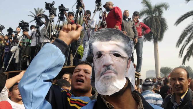 FILE - In this Saturday, Dec. 1, 2012 file photo, a supporter wears a mask depicting Egyptian President Mohammed Morsi at a rally in front of Cairo University in Cairo, Egypt. For most of the 85 years since its inception, the Muslim Brotherhood operated secretively as an outlawed group, working underground and often repressed by governments. But even after its political success since Hosni Mubarak's ouster, the group is still suspected of carrying on secretive operations.(AP Photo/Mohammed Asad, File)