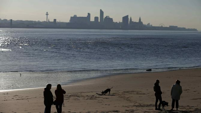 The skyline of Liverpool is seen as a people walk their dogs on New Brighton beach