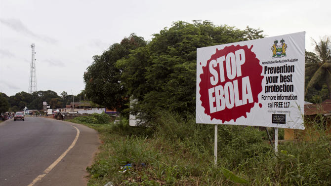 In this photo taken on Tuesday, Oct. 21, 2014, a billboard reading 'Stop Ebola' on the Masiaka Highway, forming part of a trans-West African highway, which links all West African States, on the outskirts of the capital city of Conakry, Guinea. Despite stringent infection-control measures, the risk of Ebola's spread cannot be entirely eliminated, Doctors Without Borders said Friday, Oct. 24, 2014, after one of its doctors caught the dreaded disease while working in Guinea and went to New York City. (AP Photo/ Youssouf Bah)