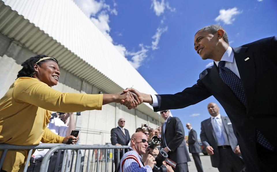 President Barack Obama reaches over to greet a supporters on the tarmac upon his arrival on Air Force One, Monday, Sept. 24, 2012, at JFK airport in New York. (AP Photo/Pablo Martinez Monsivais)
