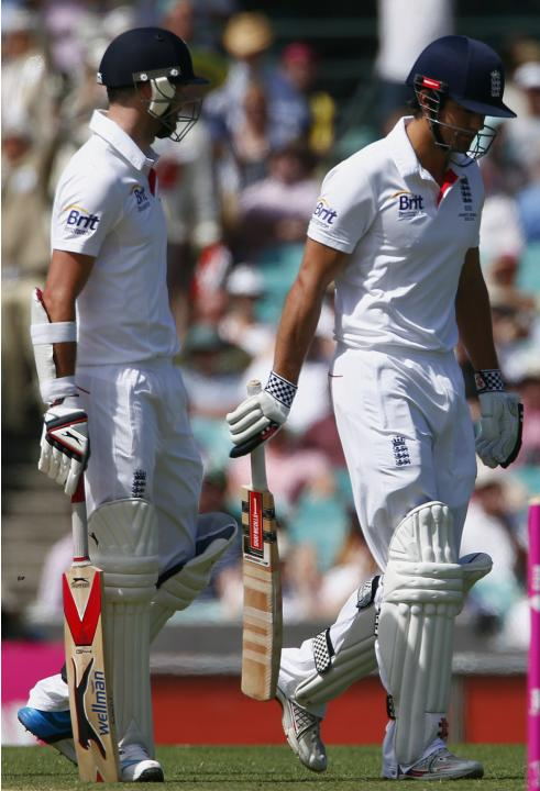 England's captain Cook reacts as he walks past teammate Anderson after being dismissed for seven runs during the second day of the fifth Ashes cricket test against Australia at the Sydney cricket