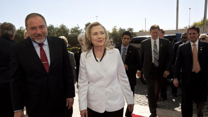 U.S. Secretary of State Hillary Rodham Clinton, center, walks with Israeli Foreign Minister Avigdor Lieberman, left, before their meeting in the Foreign Ministry in Jerusalem, Monday, July 16, 2012. Although Monday's agenda is designed to cover the breadth of U.S.-Israeli relations, the lack of action on peace talks between Israel and the Palestinians will be in the spotlight. (AP Photo/Sebastian Scheiner)