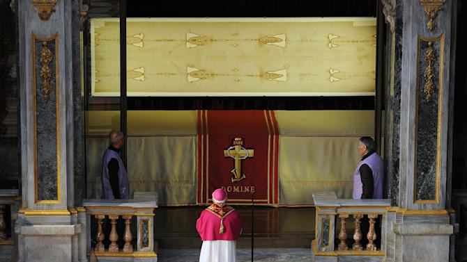 """Archbishop of Turin Cesare Nosiglia, center, kneels in front of the Shroud of Turin that went on display for a special TV appearance Saturday, March 30, 2013. The Shroud went on display amid new research disputing claims it's a medieval fake and purporting to date the linen some say was Jesus' burial cloth to around the time of his death. Pope Francis sent a special video message to the event in Turin's cathedral, but made no claim that the image on the shroud of a man with wounds similar to those suffered by Christ was really that of Jesus. He called the cloth an """"icon,"""" not a relic — an important distinction. """"This image, impressed upon the cloth, speaks to our heart and moves us to climb the hill of Calvary, to look upon the wood of the Cross, and to immerse ourselves in the eloquent silence of love,"""" he said. (AP Photo/Alessandro Di Marco, Pool)"""