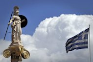 <p>A low cloud is seen behind a Greek flag and the statue of the ancient goddess Athina, patron of Athens. German Foreign Minister Guido Westerwelle has ruled out any renegotation of Greece's budget austerity programme in an interview.</p>