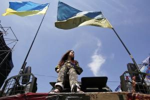 A woman sits on an armoured personnel vehicle during a rally at Independence Square in Kiev