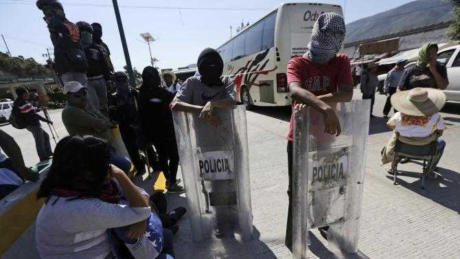 Masked CETEG members hold shields as they block the road to Acapulco on the outskirts of Chilpancingo