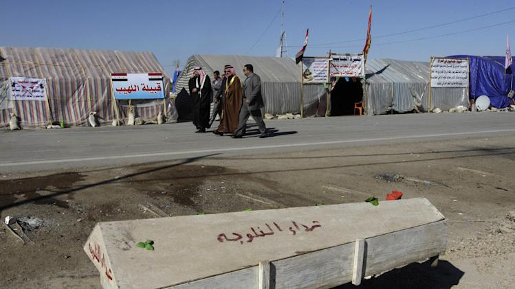 In this Monday, Feb. 18, 2013 photo, people pass a symbolic coffin for slain protesters, who were killed during protests against Iraq's Shiite-led government in Fallujah last month, at the demonstration site on the highway, which links Iraq with Jordan, in Ramadi, 70 miles (115 kilometers) west of Baghdad, Iraq. The Sunni tribesmen camped out on the edge of this one-time Iraqi insurgent stronghold are digging in and growing more organized, vowing to keep up their protests against a Shiite-led government they feel has left them behind. (AP Photo/ Khalid Mohammed)