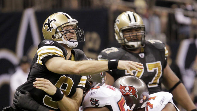 New Orleans Saints quarterback Drew Brees (9) reacts as he is hit by Tampa Bay Buccaneers outside linebacker Dekoda Watson (56) and defensive end Michael Bennett (71) during the second quarter of an NFL football game in New Orleans, Sunday, Nov. 6, 2011. (AP Photo/Bill Haber)