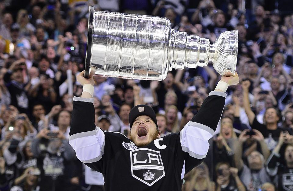 Los Angeles Kings right wing Dustin Brown (23) holds up the Stanley Cup after the Kings beat the New Jersey Devils 6-1 during Game 6 of the NHL hockey Stanley Cup finals, Monday, June 11, 2012, in Los Angeles. (AP Photo/Mark J. Terrill)