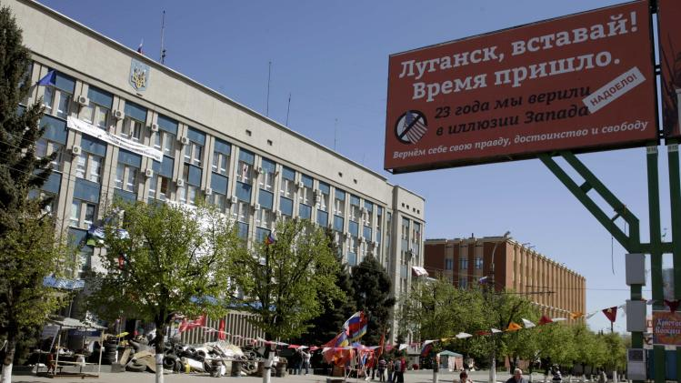 People stand outside the seized office of the SBU state security service in Luhansk