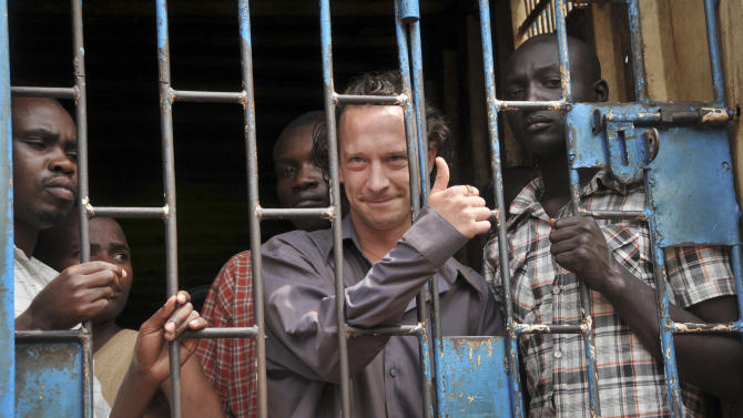 "David Cecil, the British producer of the play ""The River and the Mountain"" concerning the condition of Uganda's gays, stands in a court cell in the capital Kampala, Uganda Thursday, Sept. 13, 2012. Cecil appeared in court Thursday charged with ""disobeying lawful orders"" from the Uganda Media Council which says he staged ""The River and the Mountain"" in Uganda's capital last month despite orders to the contrary, and according to his lawyer was not released on bail because his passport, wanted by the magistrate, had been confiscated by the police. (AP Photo/Stephen Wandera)"