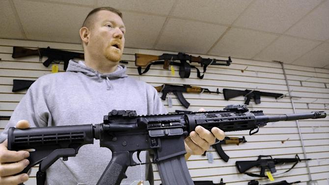 This Jan. 16 file photo shows John Jackson, co-owner of Capitol City Arms Supply, with an AR-15 rifle for sale at his business in Springfield, Ill.  From Oregon to Mississippi, President Barack Obama's proposed ban on new assault weapons and large-capacity magazines struck a nerve among rural lawmen and lawmakers, many of whom vowed to ignore any restrictions and even try to stop federal officials from enforcing gun policy in their jurisdictions.  (AP Photo/Seth Perlman)