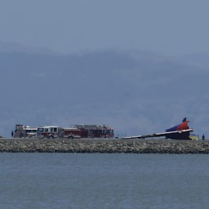 The tail of Asiana Flight 214 is seen, right, after …