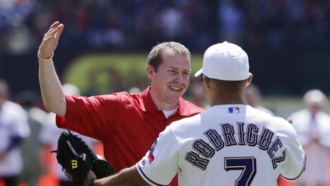 Robbie Parker, left, receives a hug from Texas Rangers representative Ivan Rodriguez (7) after throwing out the ceremonial first pitch before a baseball game between the Los Angeles Angels and Texas Rangers Friday April 5, 2013, in Arlington, Texas. Parker, a North Texas native whose 6-year-old daughter, Emilie, was among the victims of the Sandy Hook school shooting in Connecticut, threw out the first pitch before the Rangers home opener, their favorite team. (AP Photo/Tony Gutierrez)