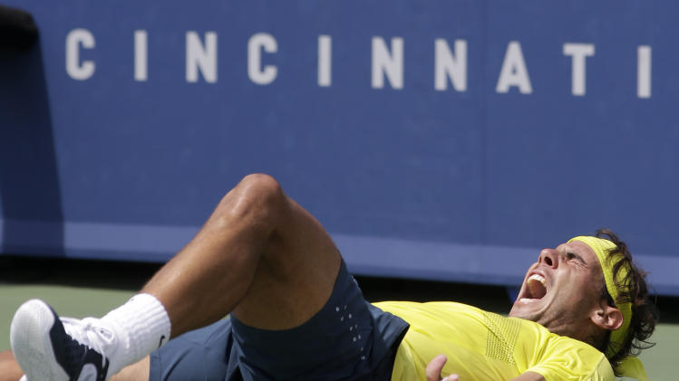 Rafael Nadal, from Spain, falls to the court after defeating John Isner 7-6 (8), 7-6 (3) to win the Western & Southern Open tennis tournament on Sunday, Aug. 18, 2013, in Mason, Ohio. (AP Photo/Al Behrman)