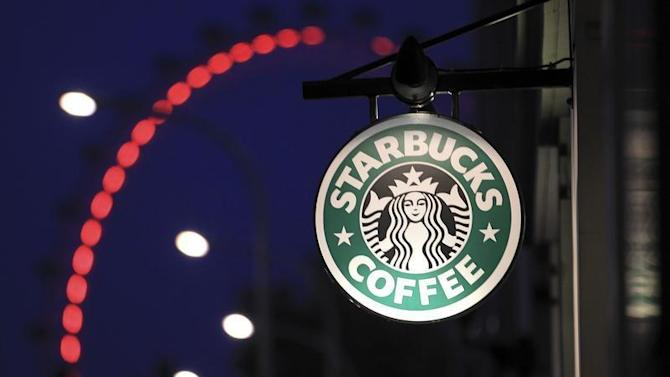 The sign outside a Starbucks coffee shop on in Westminster is seen with the London Eye in the background, in central London