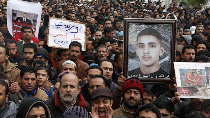 "Protesters chant slogans and hold a picture of a slain young man in Port Said, Egypt, Friday, Feb. 1, 2013. Protests were held in cities around the country on Friday after a call for rallies by opponents of Islamist President Mohammed Morsi. But some cracks appeared in the ranks of the opposition as some sharply criticized its political leaders for holding their first meeting with the rival Muslim Brotherhood a day earlier. Arabic on the placard at center reads ""Port Said, the red line for Morsi."" (AP Photo/Aly Hazzaa, El Shorouk Newspaper) EGYPT OUT"