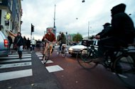 Commuters ride their bicycles in late afternoon traffic near Amsterdam Central Station on November 2, 2012