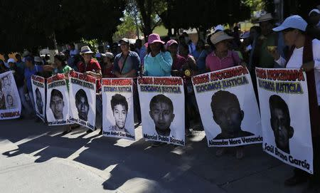 Relatives hold pictures of missing students of the Ayotzinapa Teacher Training College Raul Isidro Burgos, during a protest march demanding the government find them, in Zumpango, in the southern Mexican state of Guerrero
