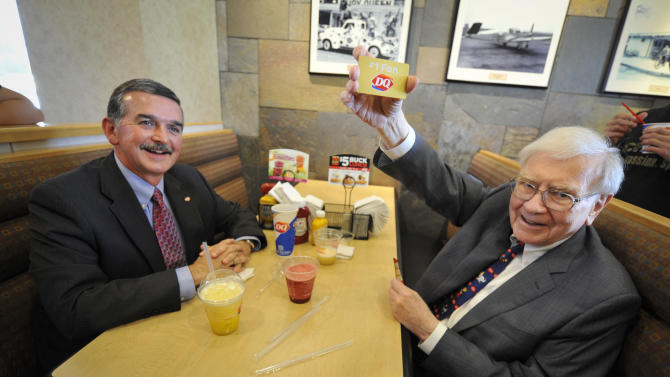 """IMAGE DISTRIBUTED FOR DAIRY QUEEN - Berkshire Hathaway's Warren Buffett, right, and Dairy Queen's CEO John Gainor hold a gold gift card, Monday May 20, 2013 in Omaha, Neb.  Buffet helped launch the """"The First S'mores Blizzard of Summer"""" and was celebrated as Dairy Queen's number one fan.  (Dave Weaver/AP Images for Dairy Queen)"""