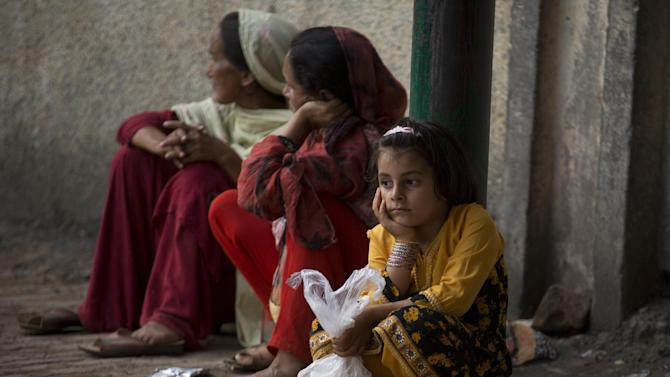 FILE - In this Thursday, July 23, 2015, file photo, a Pakistani family waits for more food donations at a distribution center at a local shrine in Islamabad, Pakistan. (AP Photo/B.K. Bangash, File)