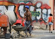 <p>A construction worker works pushes a wheelbarrow in Bucharest on August 10. The recovery in Romania's economy after two years of severe recession is now coming under threat, analysts warn, victim to the months-long political crisis that has engulfed the EU country.</p>