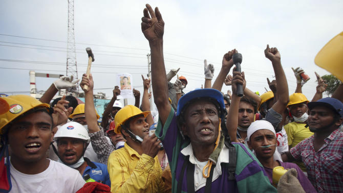 In this photo taken on Sunday April 28, 2013, volunteer workers protest when they were told that the search would have to stop as they want to continue searching for victims believed to be alive and still trapped. When the Rana Plaza, a garment factory building collapsed, many of the first responders were neighborhood residents, fellow garment workers, relatives of the missing and charity workers, and they repeatedly took some of the most dangerous work.(AP Photo/Wong Maye-E)