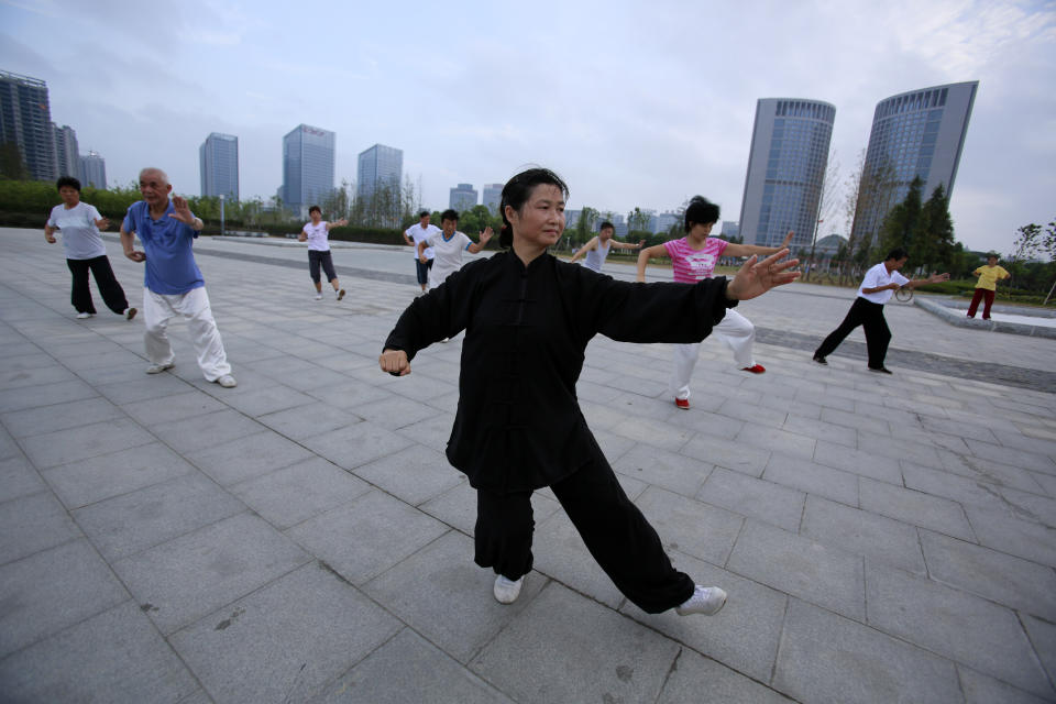 People practice tai-chi at a park near the Hefei City Intermediate People's Court Wednesday Aug. 8, 2012  in Hefei, Anhui Province, China. The murder trial of Gu Kailai, wife of ousted Chinese politician Bo Xilai, will start Thursday at the court. (AP Photo/Eugene Hoshiko)