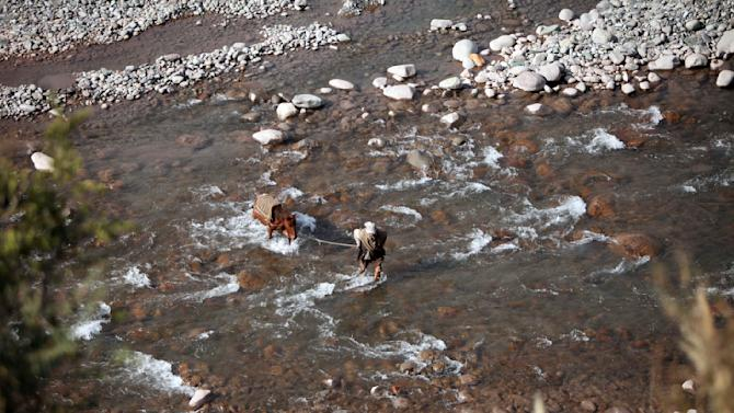 An Indian man along with his horse tries to cross the River Betar near the border village of Dallan, in Poonch, 250 kilometers (155 miles) northwest of Jammu, India, Tuesday, Jan. 15, 2013. India's army chief Gen. Bikram Singh on Monday accused Pakistan of planning an attack in which two Indian soldiers were killed in the disputed Kashmir region last week, and warned of possible retaliation. (AP Photo/Channi Anand)