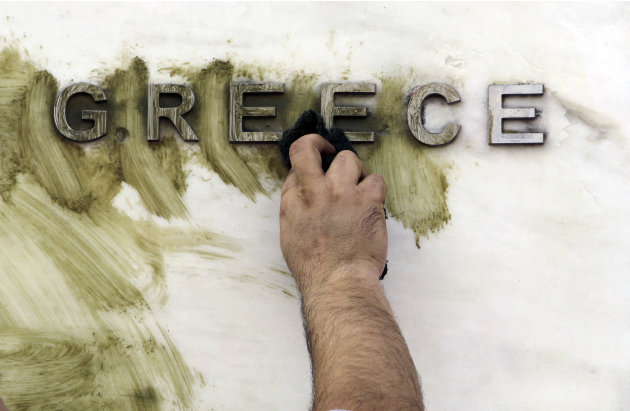 A worker cleans graffiti off the Bank of Greece logo, outside the central bank's headquarters in Athens, Monday, Nov. 26, 2012. The ministers of the 17 countries that use the euro are meeting in Bruss