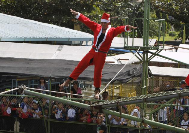 A man walks on a tight rope over live crocodiles while wearing a Santa Claus costume as part of performances for the Yuletide season at a crocodile farm in Pasay city