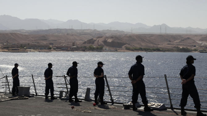 U.S. Navy sailors stand in formation as the the USS Stockdale leaves port for maneuvers with the Jordanian Navy in the Gulf of Aqaba, Jordan as part of Eager Lion, a multinational military exercise, Tuesday, June 18, 2013. Under the watchful eye of stern-faced American advisers, hundreds of U.S.-trained Jordanian soldiers are holding war games that could eventually form the basis of an assault in Syria. There is fear of spillover from the Syrian war in this U.S.-allied kingdom, and the potential for a Jordanian role in securing Syria's chemical stockpiles should Bashar Assad's regime lose control. (AP Photo/Maya Alleruzzo)
